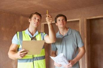 Builder And Inspector Looking At New Property
